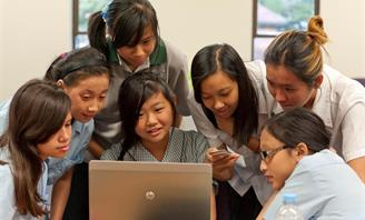 Photo of a group of school girls using a computer