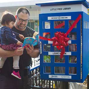 Photo of a father and daughter using the Little Free Library